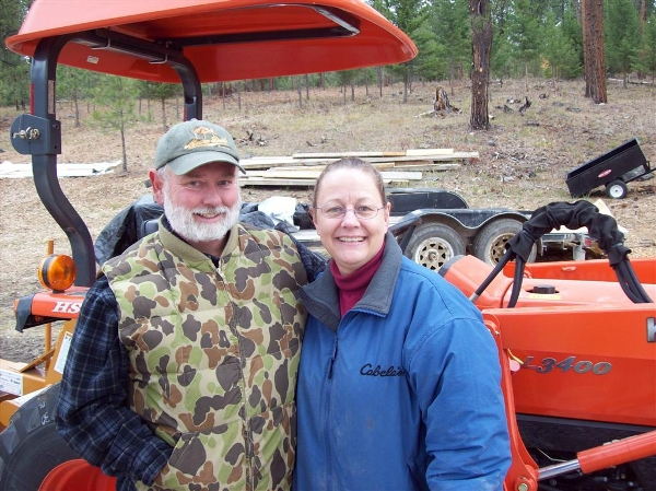 Husband and wife standing beside Kubota tractor