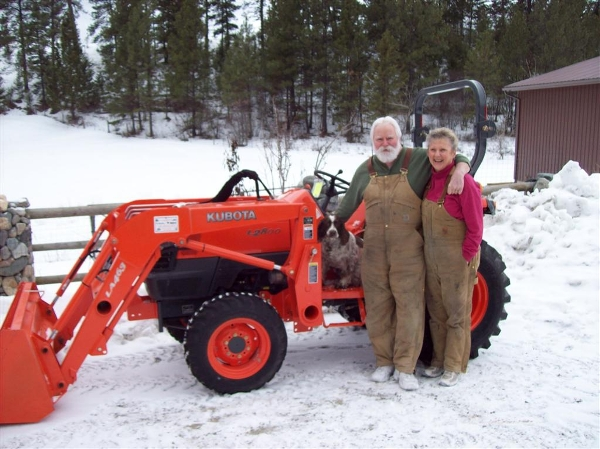 Husband and wife standing beside Kubota tractor with dog