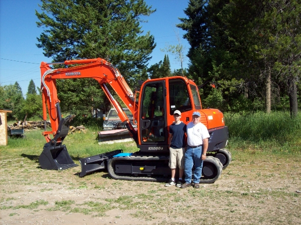 Man and boy standing in front of Kubota mini excavator