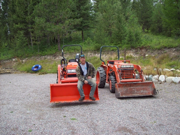 Man sitting on bucket of Kubota tractor