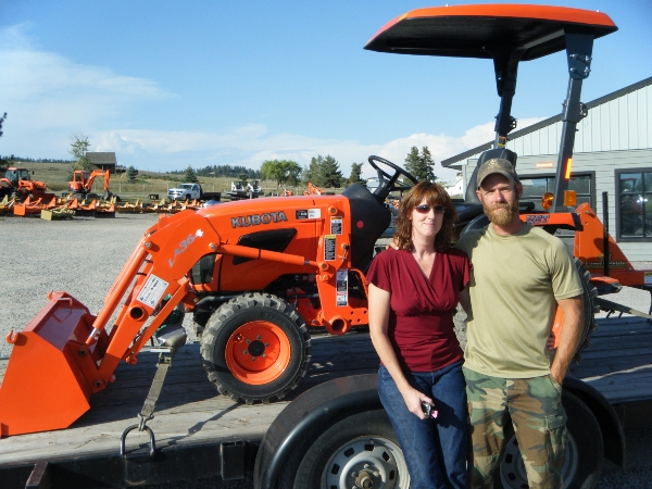 Husband and wife standing in front or trailered Kubota tractor