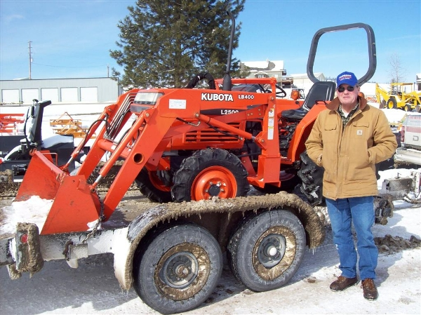 Man standing in front or trailered Kubota tractor