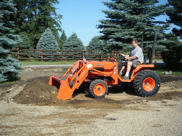 Man using Kubota tractor to move dirt