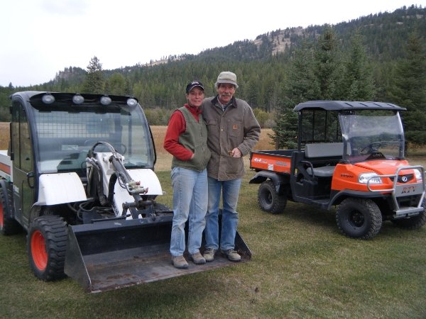 Husband and wife standing in Bobcat ATV bucket