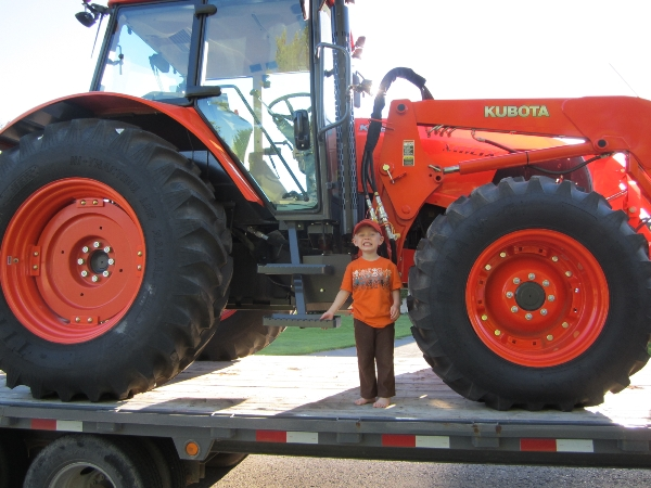 Small boy standing in front of Kubota tractor