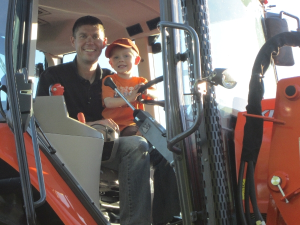 Boy sitting with dad in Kubota tractor