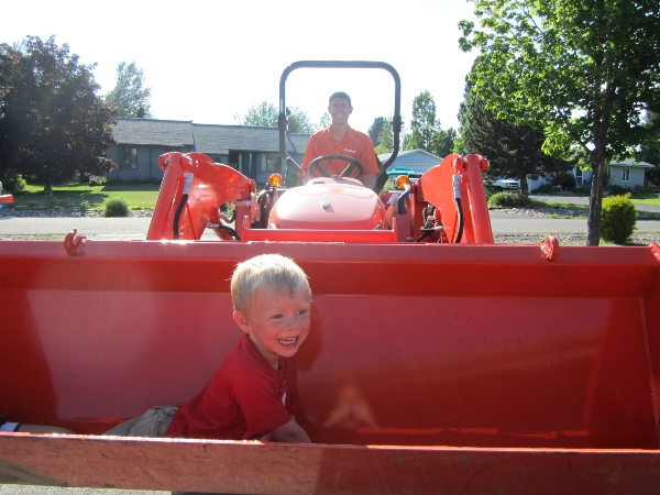 Boy in bucket of Kubota tractor