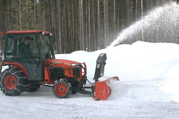 Removing snow with Kubota tractor and snowblower attachment