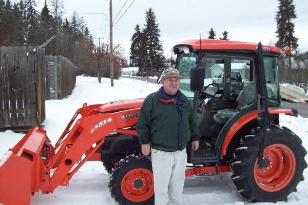 Man Standing in front of kubota tractor