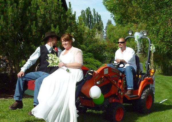 Birde and Groom siiting in bucket of Kubota tractor