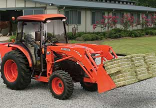 used equipment for sale - Kubota tractor with hay bales